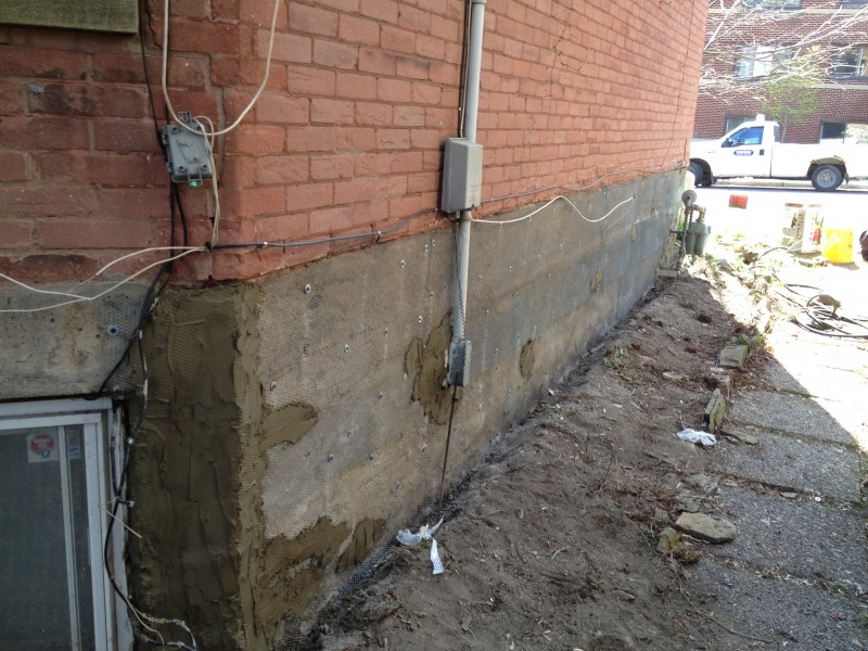 applying a base coat of parging to a concrete foundation